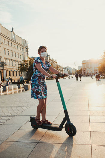 Young woman riding an electric scooter in the city center. woman wearing the face mask