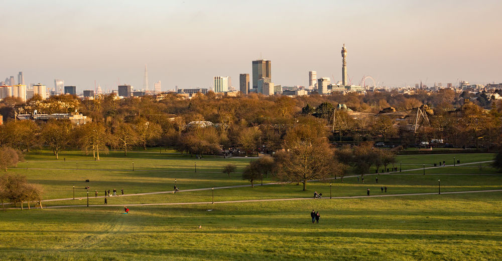 People at primrose hill park in city against sky during sunset