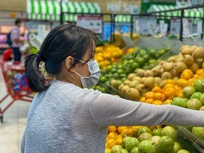 Midsection of woman with fruits at market stall
