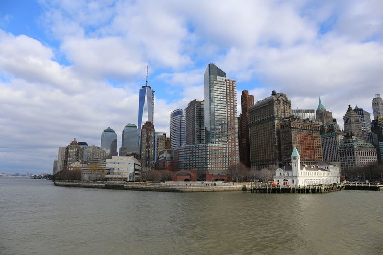 City buildings at waterfront against cloudy sky