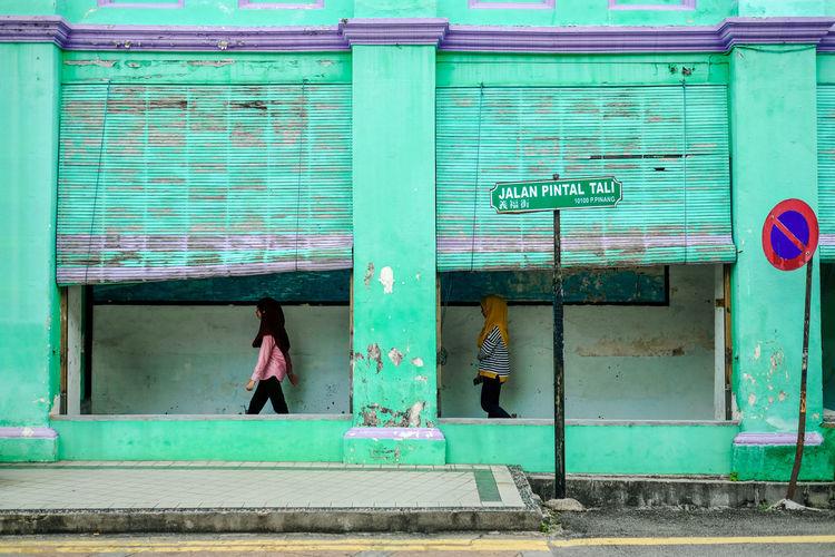Side View Of Women Walking On Sidewalk