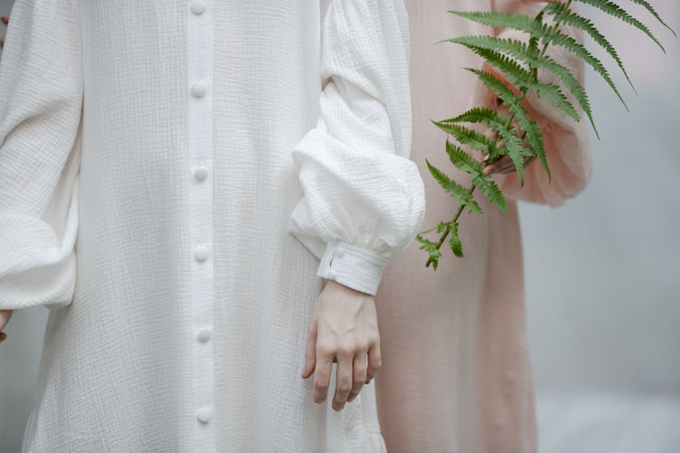 Midsection of women standing with plant