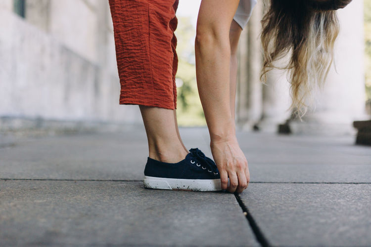 Low section of women standing on street bending forward