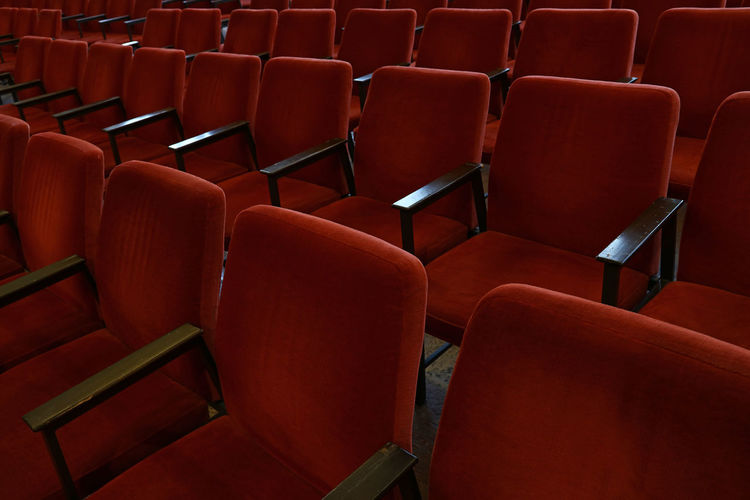 Empty red chairs in row at theater