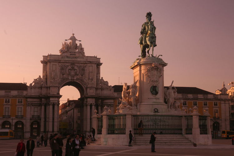 Low angle view of statue and building against sky at praca do comercio