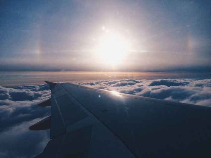 Aerial view of airplane wing over sea against sky during sunset