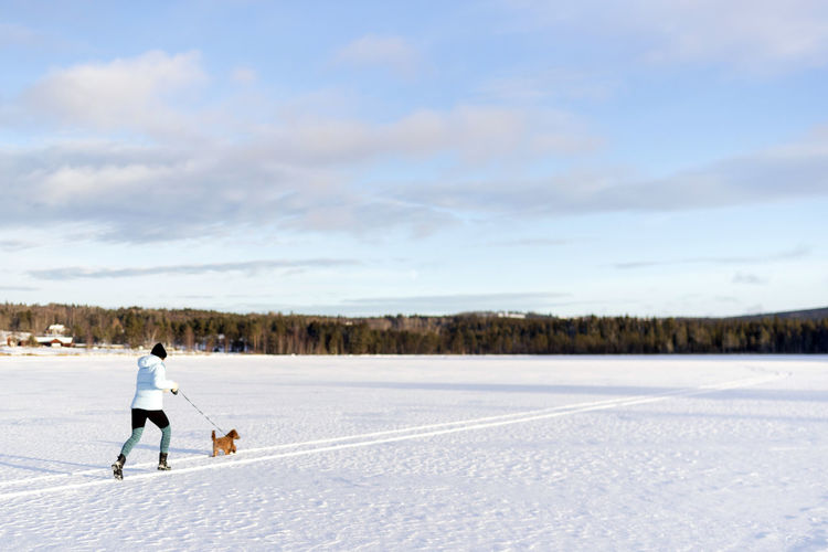 Woman with dog on snowy field against sky