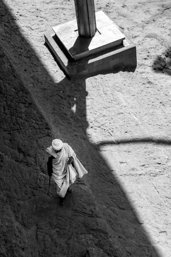 Aerial view of robed holy man walking amongst the rock-hewn churches of lalibela, ethiopia.