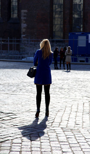 Rear view of woman standing on paved footpath