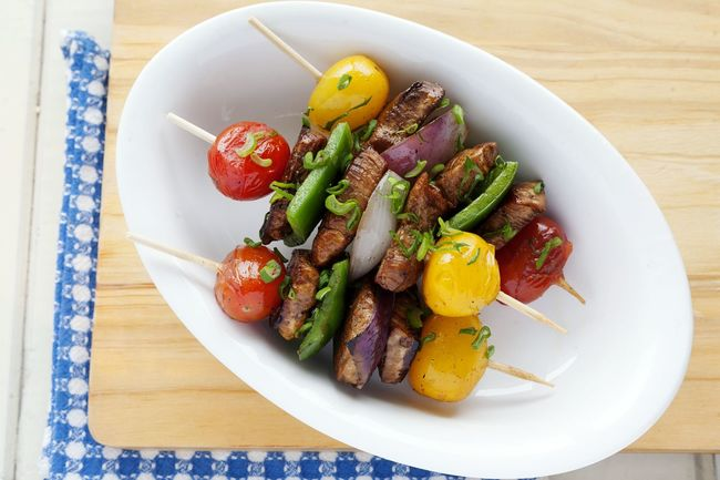 Skewers of chicken and vegetables in a Porcelain dish. Food And Drink Healthy Eating Indoors  No People Ready-to-eat Natural Light Porcelain  Unykaphoto Chicken Skewers Skewered Chicken Green Pepper Grilled UnykaProductions Cherry Tomatoes Red Onion Scallions Yellow Cherry Tomato Studio Photography Multi Colored Checkered Napkin Blue Napkin Cutting Board Wooden Background White Background Food Stories