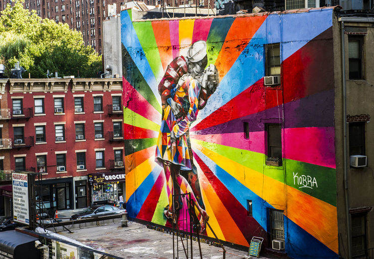 Beautiful multi colored mural on a large wall in NYC Architecture Art Building Exterior Built Structure City Day Graffiti Multi Colored Mural Mural Art No People Outdoors Tree
