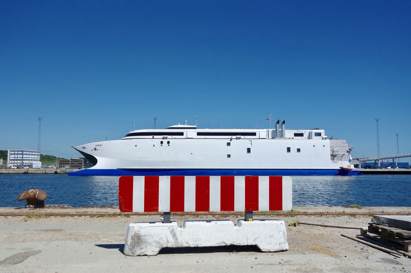 Ship moored at harbor against clear blue sky