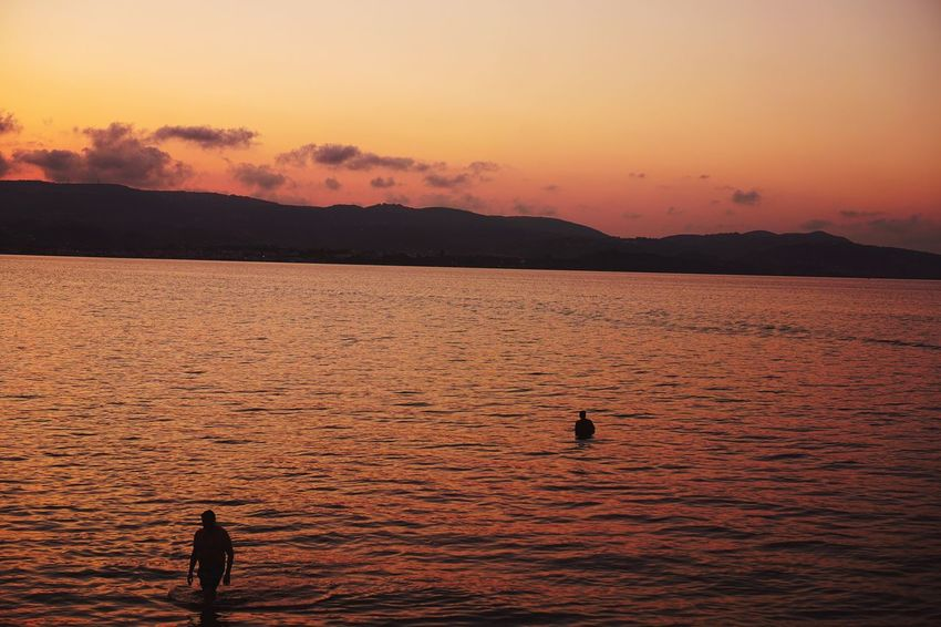 Sunset Beauty In Nature Silhouette Nature Water Scenics Real People Mountain Orange Color Sea Outdoors Sky Tranquil Scene Healthy Lifestyle Enjoying Life Leisure Activity Tranquility Men Lifestyles Vitamin Sea The Week On EyeEm Enjoying The View Real Photography Colors Beauty In Nature