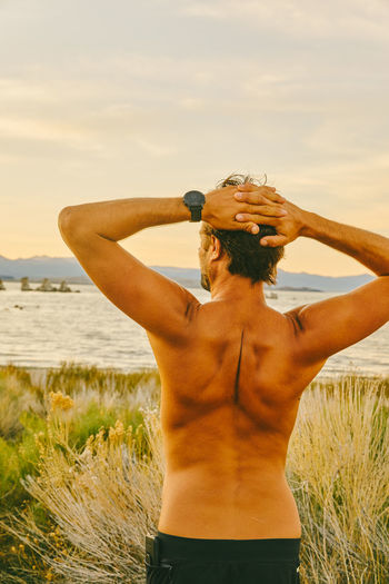 Rear view of shirtless man standing at beach against sky