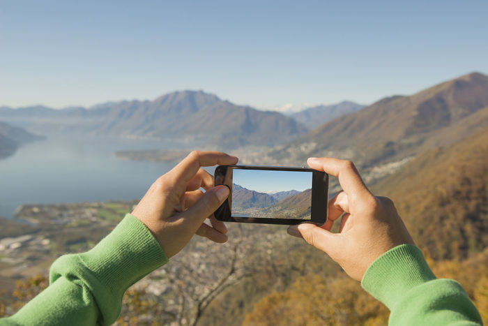 Woman Taking a Photo of the Mountain and Alpine lake Maggiore with Mobile Phone in Ticino, Switzerland. Clear Sky Color Communication Elevated View Filming Full Frame Human Hand Idyllic IPhone Lake Lake Maggiore Landscape Mountain Panoramic View Personal Perspective Photography Photography Themes Point Of View Scenics Smart Phone Swiss Alps Tranquility Using Phone Wifi Woman