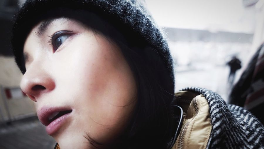 Close-Up Of Young Woman Wearing Knit Hat In City During Winter