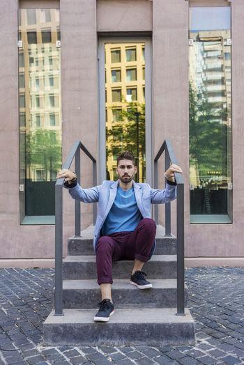 Portrait of handsome man sitting on steps against building
