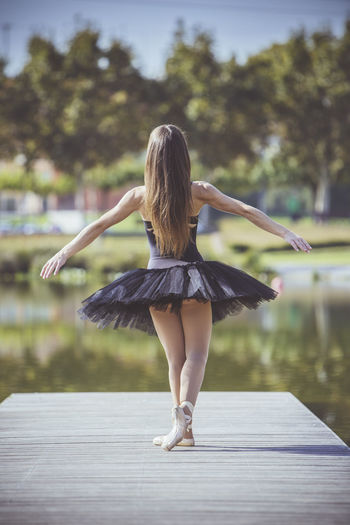 Rear View Of Woman Ballet Dancing On Pier Over Lake