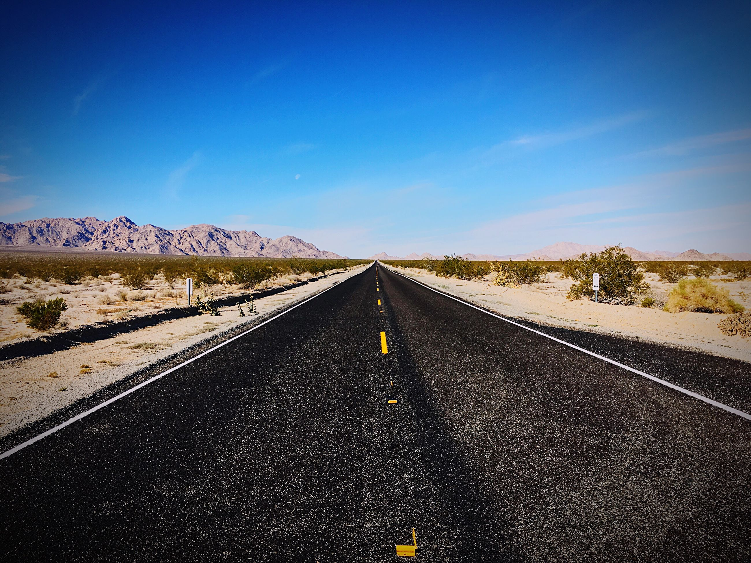 the way forward, road, vanishing point, road marking, diminishing perspective, transportation, asphalt, white line, no people, nature, landscape, outdoors, day, sky, straight, scenics, dividing line, tranquility, mountain, beauty in nature, clear sky
