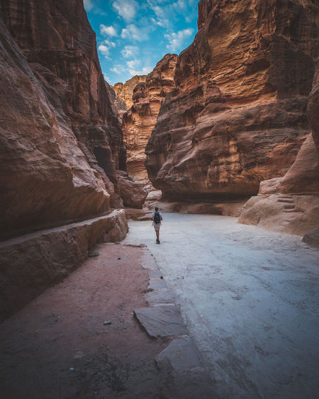 Rock Real People Rock Formation One Person Lifestyles Scenics - Nature Mountain Nature Beauty In Nature Walking Tranquility Outdoors Mountain Range Men Petra Jordan Jordanie Middle East Oriental Desert Arid Climate Blue Sky Canyon Valley Crazy Place