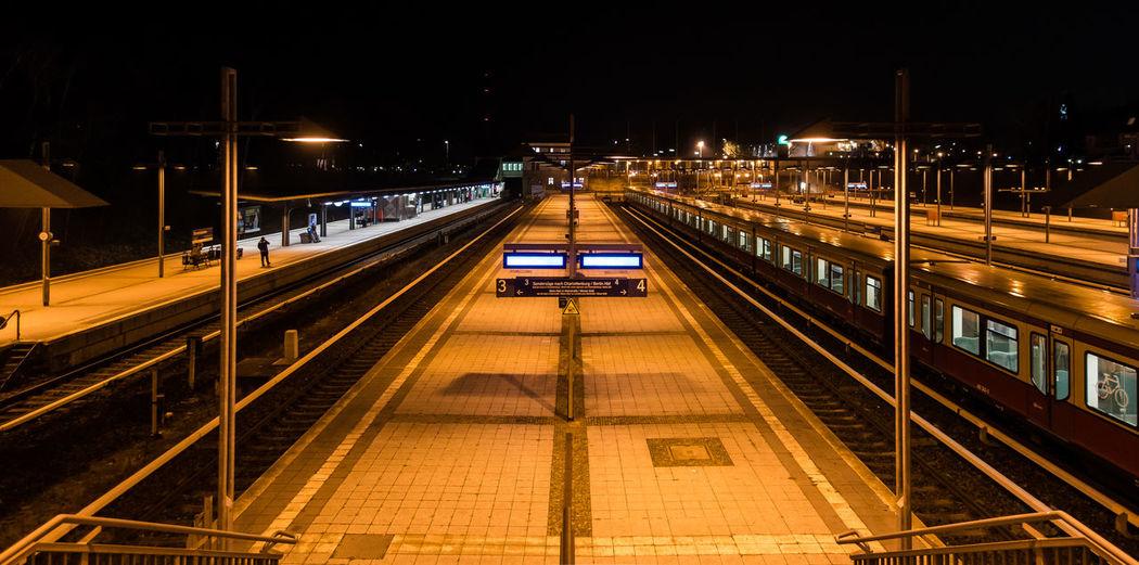 High angle view of illuminated railroad station platforms at night