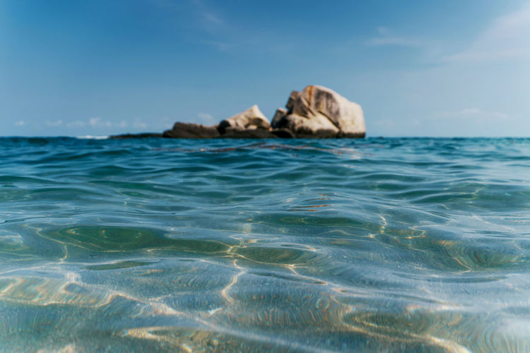 surface level photograph of rock formation surrounded by the blue sea in Koh Tao, Thailand Water Sea Waterfront Sky Scenics - Nature Beauty In Nature Day Tranquility Tranquil Scene Nature Rock No People Idyllic Rippled Blue Surface Level Horizon Horizon Over Water Outdoors Rock Rock - Object Rock Formation Harmony Harmony With Nature Relaxing Relaxation Calm Calmness Calm Water Quiet Tranquility
