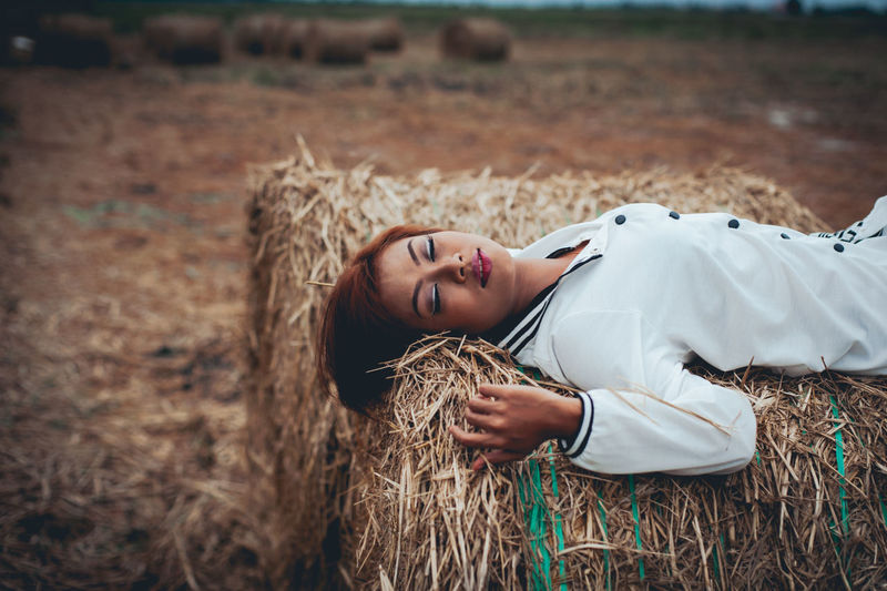 High angle view of young woman lying on hay bale at farm