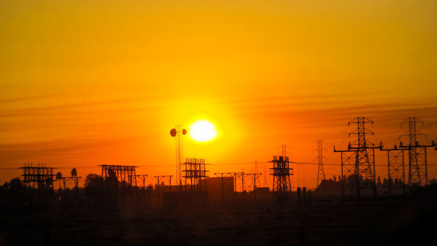 Silhouette electricity pylons against orange sky during sunset