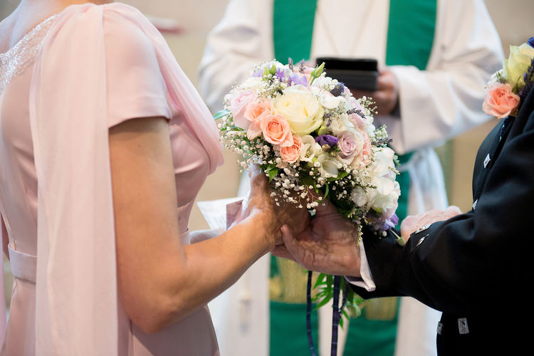 Midsection Of Bride And Bridegroom Holding Bouquet By Priest At Church