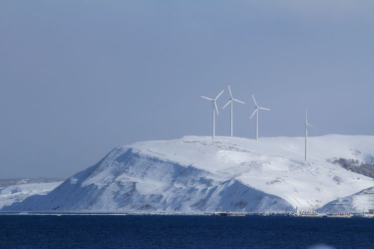 Scenic view of snowcapped mountains with wind turbines against sky