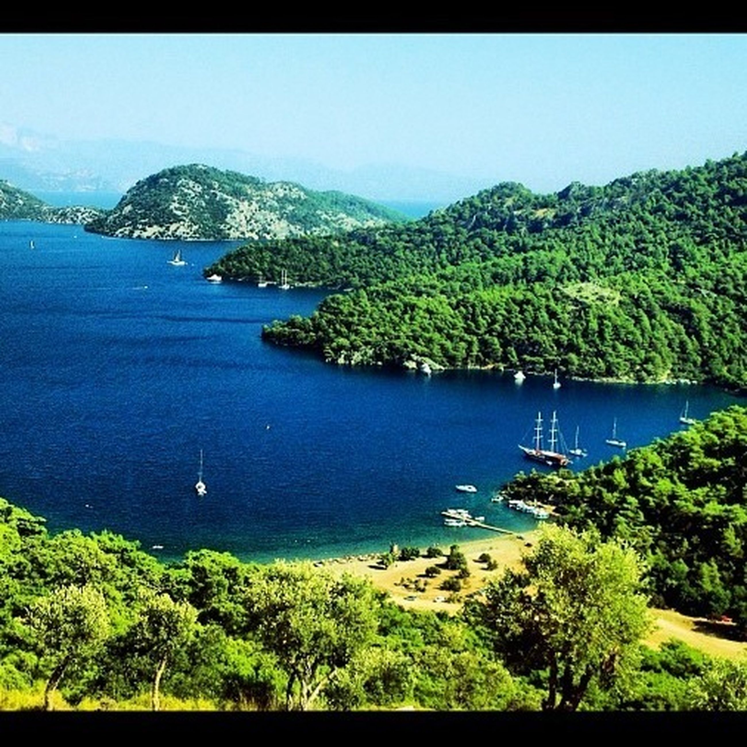 water, sea, mountain, tranquil scene, tree, clear sky, tranquility, scenics, blue, beauty in nature, nautical vessel, nature, boat, coastline, idyllic, high angle view, copy space, transportation, green color, day