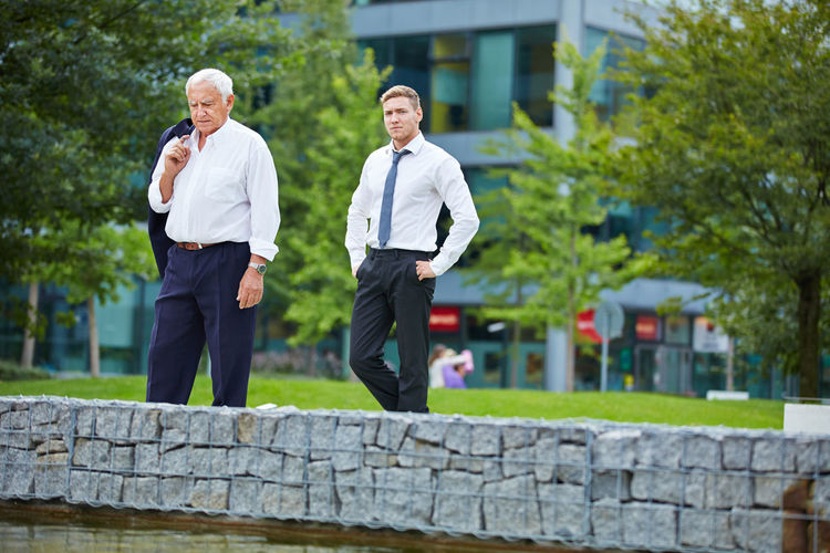 Portrait Of Young Businessman Standing By Senior Colleague In Park