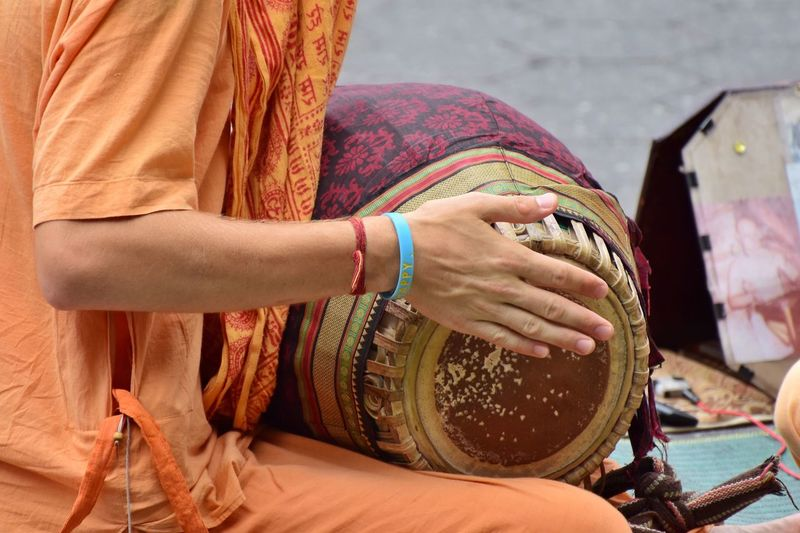 Midsection of man wearing traditional clothes banging drum outdoors