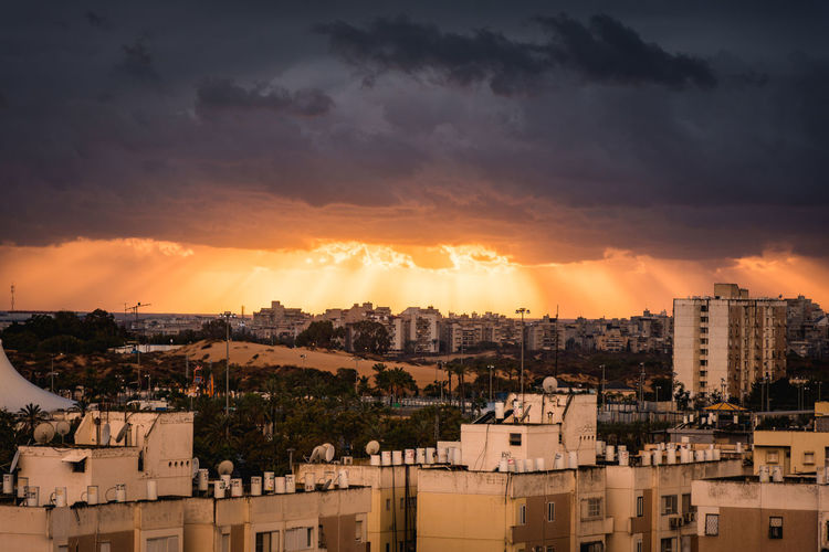 Sunset Before The Storm ☔ ⚡ 🌇 Glimpse Of The Sun ☀ Between The Clouds And The Mighty Nature -ISRAEL Architecture Building Exterior City City Cityscape Cloud - Sky Dramatic Sky Exploring Style My Year My View No People Outdoors Power In Nature Sunbeam Sunlight Sunset Sunset_collection Urban Skyline Finding New Frontiers The City Light Shades Of Winter