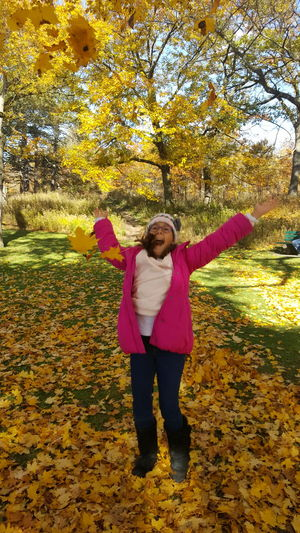 Full length of woman with arms raised standing in autumn
