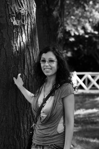 Portrait of smiling young woman standing against tree trunk