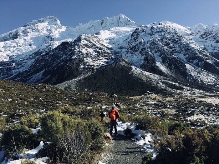Rear view of people on footpath by snowcapped mountains