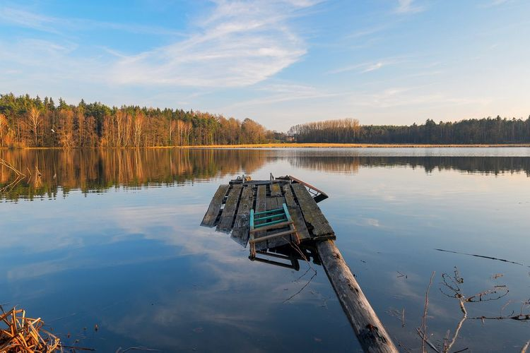 A broken jetty at a lake under blue sky