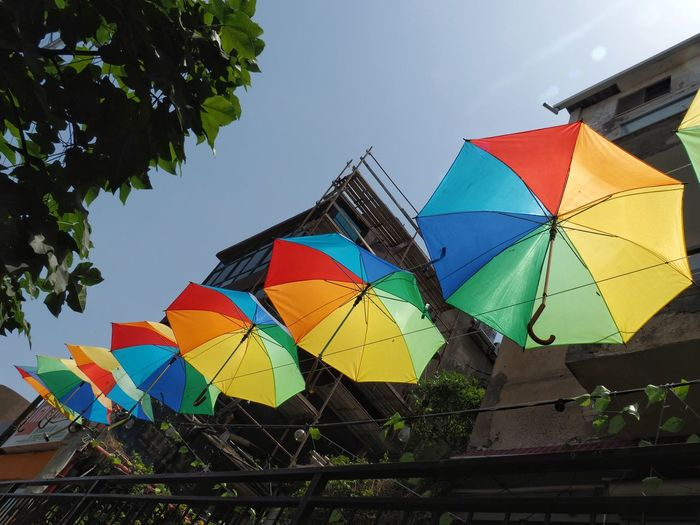 Low angle view of multi colored umbrellas against sky