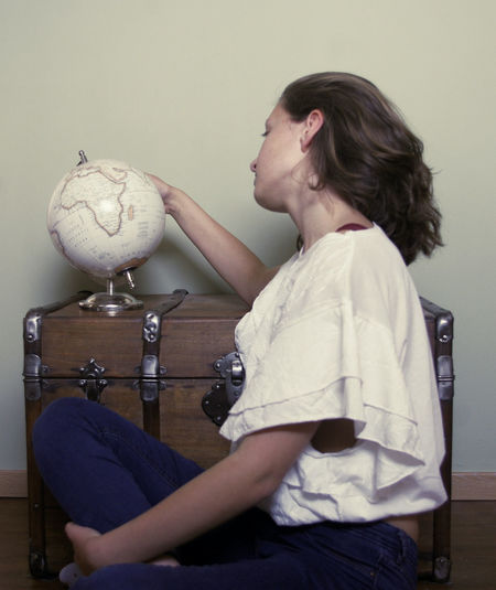 Side view of a young woman looking away against wall