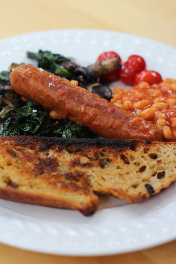 English breakfast served on a plate Baked Beans Brunch Close-up Day English Breakfast Food Food And Drink Freshness Indoors  Kale Meat No People Plate Ready-to-eat Sausage Toasted Bread Tomatoes Vegan Food Vegan Sausage