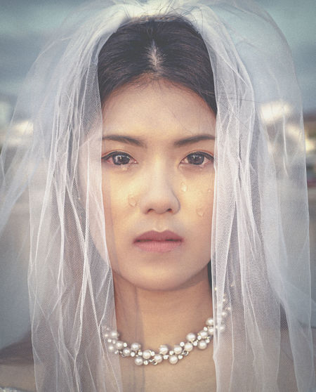 Portrait of crying bride standing at wedding ceremony