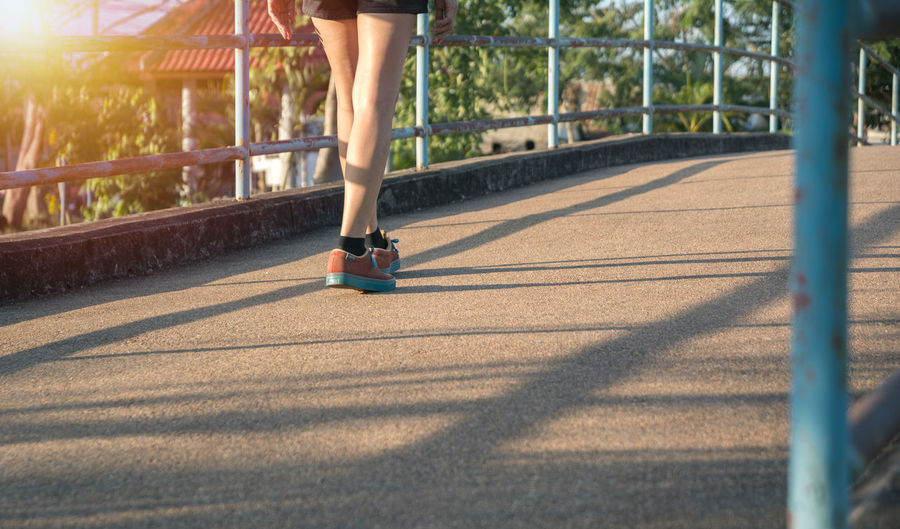 A woman running at the morning for jogging, exercising and healthy lifestyle concept. Sport Shadow Sunlight Low Section One Person Human Leg Women Real People Body Part Lifestyles Adult Human Body Part Shoe Nature Day Healthy Lifestyle Leisure Activity Track And Field Running Outdoors Human Foot Human Limb Shorts