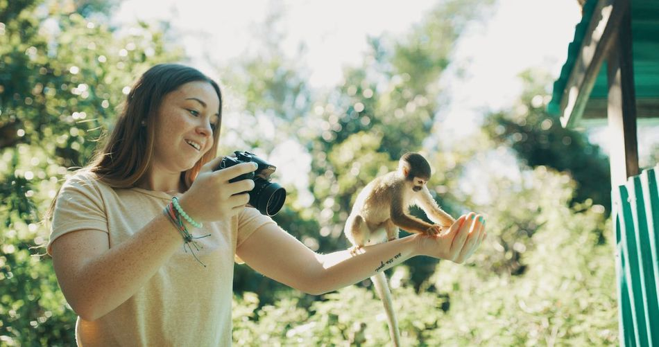 Young woman holding camera while standing on land