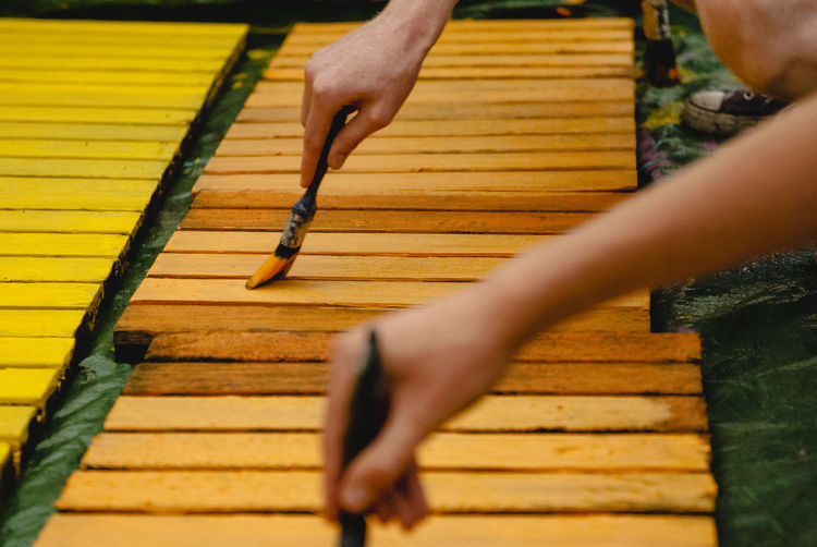 Cropped image of people painting wooden planks outdoors