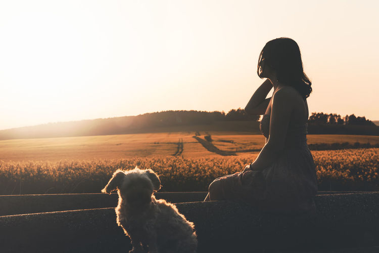 Side view of woman sitting with dog during sunset