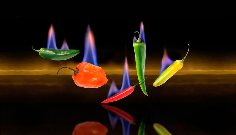 Hot peppers of several types are seen with flames to illustrate their heat. Dark background. Photo illustration. Dark Flames Hot Hot Pepper Reflected Glory Spicy Food Blue Flames Childhood Flaming Hot Food Habanero Jalapeno Pepper Sky Spice Thai Pepper