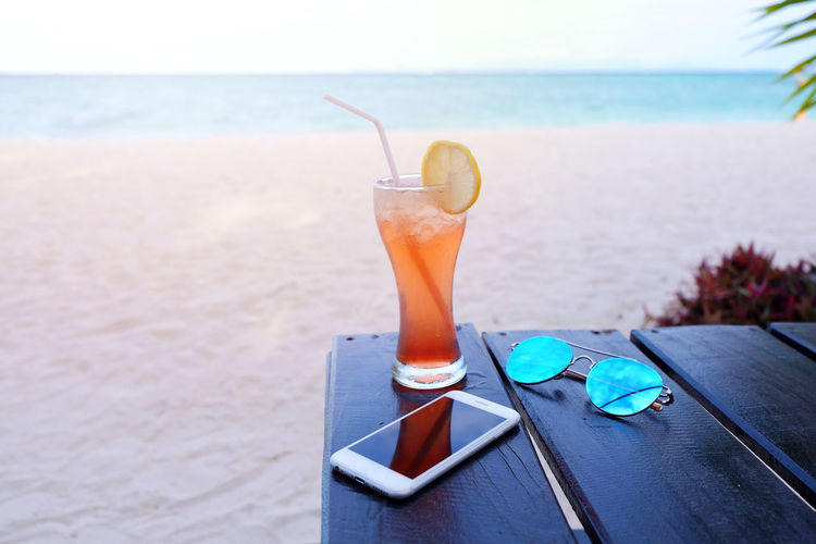 Holiday Summertime Vacations Alcohol Beach Cocktail Day Drink Drinking Glass Drinking Straw Food And Drink Glass Horizon Over Water Household Equipment Land Nature No People Outdoors Refreshment Sea Smart Phone Straw Sunglasses Table Water