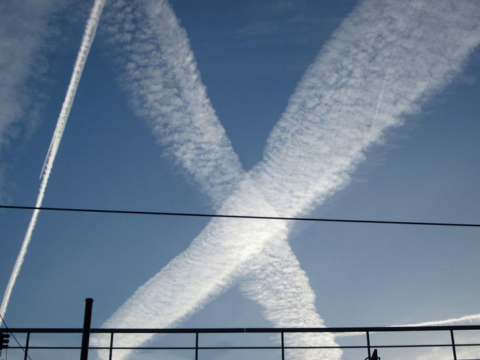 pair of contrails forming a white cross against the blue sky Contrails White Cross Blue Sky View Fence Gate Airplane Condense Plane Flying Vapor Trail No People Nature Outdoors Air Pollution White Color Smoke - Physical Structure Day