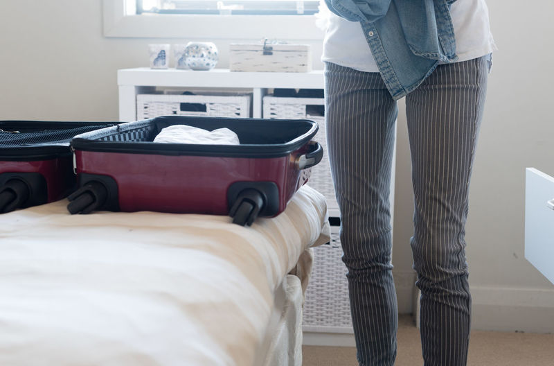Woman packing clothes in red suitcase in bedroom Adult Bed Bedroom Casual Clothing Day Domestic Room Furniture Indoors  Jeans Lifestyles Low Section Luggage Luxury Midsection One Person Real People Standing Suitcase Travel Women